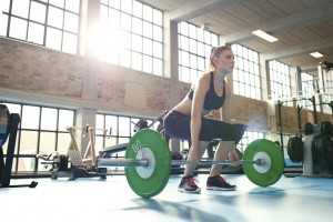 Determined and strong fitness woman training with heavy weights in fitness club. Caucasian female athlete doing weight lifting exercise in gym.