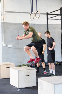 A group trains at a gym center. One man do box jumps and two talking in the background.