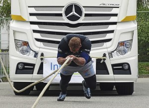 Chemnitz, Germany - October 4, 2015: A strong man pulling a 15 ton heavy truck with a rope in the final of FIROCON Truck Pull European Championships in Chemnitz (Germany). During the two-day championships, the most powerful men and women in Europe measured their forces. The athletes came from Germany, Poland, The Netherlands, Italy, Switzerland, Austria, Czech Republic, Serbia, Ukraine, Norway and Ireland.